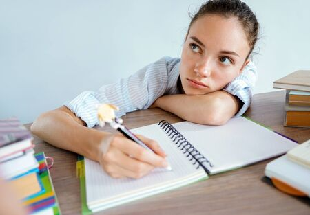 Thinking student writes an essay. Photo of girl sits at the table and looks away. Education concept