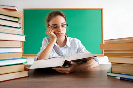 Student reads boring book. Photo of girl wearing glasses sits surrounded by books. Education concept 스톡 콘텐츠