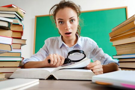 Student in shock. Photo of young girl with open mouth and big eyes, around books. Education concept