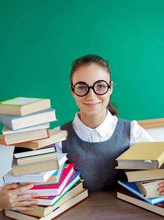 Smiling student hugs books. Photo of girl in uniform, wearing glasses. Education concept