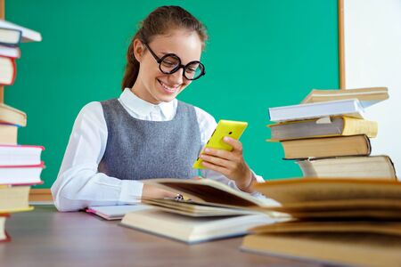 Happy girl looks at the phone and reads the message. Photo of student in uniform, wearing glasses. Education concept