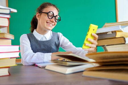 Happy girl looks at the phone and makes a selfie. Photo of student in uniform, wearing glasses. Education concept