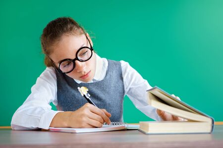 Student peeps into the book, writing off something. Photo of girl in uniform, wearing glasses. Education concept 스톡 콘텐츠