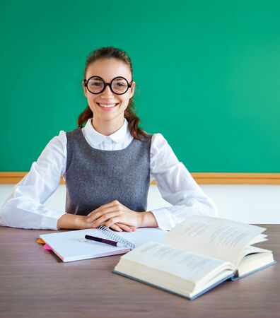 Diligent student, ready to learn. Photo of girl in uniform, wearing glasses. Education concept