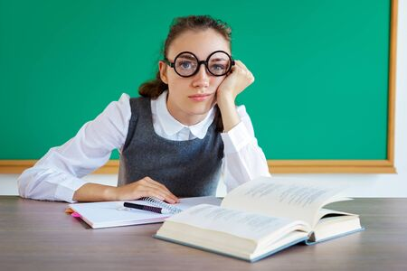 Exhausted or bored young student in classroom. Photo of student wearing glasses. Education concept