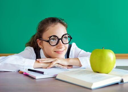 Student dreaming or thinking of something pleasant while sitting at the desk with open book. Education concept 스톡 콘텐츠