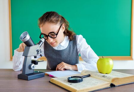 Young student looks through microscope, conducts research. Photo of girl in uniform, wearing glasses. Education concept 스톡 콘텐츠