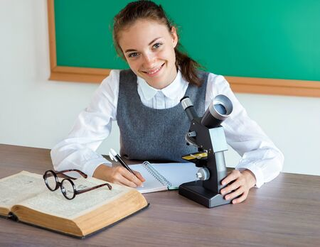 Smiling student doing research using microscope. Photo of girl in uniform, wearing glasses. Education concept