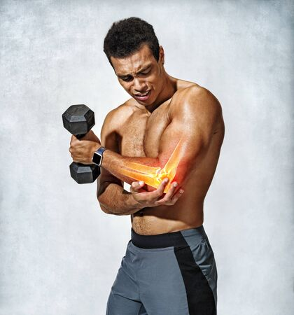 Sporty man holding his inflamed elbow. Photo of man workout on grey background. Strength and motivation Banco de Imagens