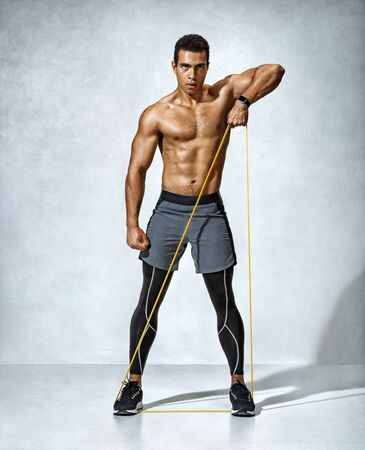 Man with athletic body performs exercises using a resistance band. Photo of muscular man on grey background. Strength and motivation. Full length