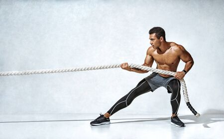 Strong man pulling rope. Photo of sporty man on grey background. Strength and motivation. Side view. Full length