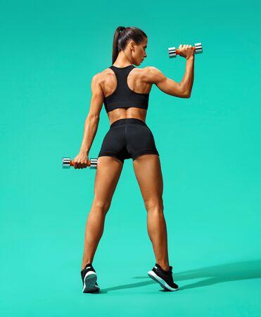Sterke vrouw die met dumbbells traint, haar arm buigt. Foto van sportieve vrouw in sportkleding op turkooizen achtergrond. Achteraanzicht. Volledige lengte