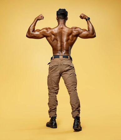 Hombre joven mostrando sus músculos. Vista trasera del culturista con físico perfecto sobre fondo amarillo. Fuerza y motivación.