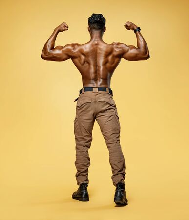 Young man showing his muscles. Rear view of bodybuilder with perfect physique on yellow background. Strength and motivation.