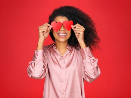 Happy girl holds red papers hearts and smiling. Photo of attractive latin girl in love on red background. Valentines Day Imagens