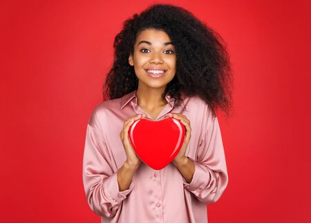 Happy girl with candy box. Photo of african american girl in love on red background. Be my Valentine
