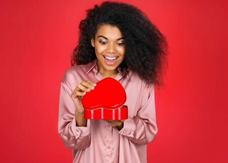 Overjoyed girl looks in the gift box. Photo of african american girl in love on red background. Be my Valentine