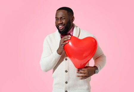 Handsome man winking. Photo of african american man in love holds red heart shape balloon on pink background Imagens