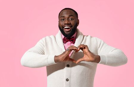 Handsome man shows heart symbol, shapes love sign with hands. Photo of african american man expresses love to someone, romantic feelings on pink background. Be my Valentine