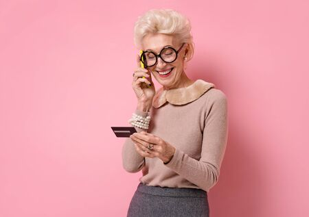 Woman reading something off her credit card while talking on the phone. Photo of kind elderly woman on pink background Stock Photo