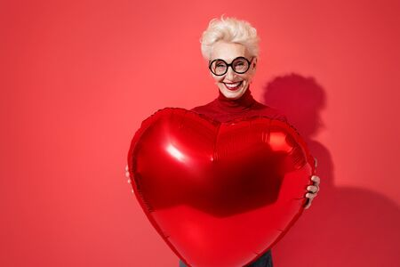 Happy woman holds red heart shape balloon. Photo of smiling elderly woman in love on red background. Valentines Day Imagens