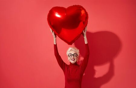 Happy woman holds red heart shape balloon over her head. Photo of smiling elderly woman in love on red background. Valentines Day