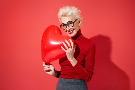 Lovely woman hugs red heart shape balloon. Photo of smiling elderly woman in love on red background. Valentines Day
