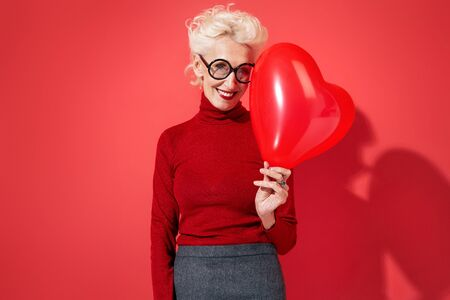 Cute woman holds red heart shape balloon. Photo of smiling elderly woman in love on red background. Valentine's Day