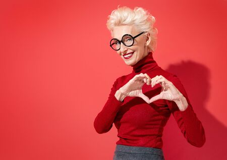 Beautiful woman shows heart symbol, shapes love sign with hands. Photo of smiling elderly woman in love on red background. Be my Valentine
