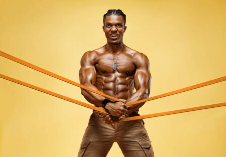 Strong man working with resistance band. Photo of man with athletic body on yellow background. Strength and motivation