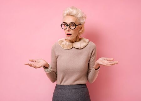 Confused beautiful grandmother spreads hands sideways, feels doubt while makes choice. Photo of kind elderly woman in eyeglasses looking at camera on pink background.