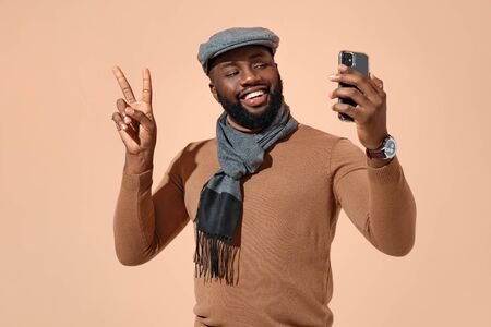 Handsome man makes video call and shows peace gesture or says hi. Photo of african american man in stylish casual clothes on beige background