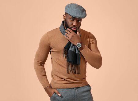 Handsome stylish man on beige background
