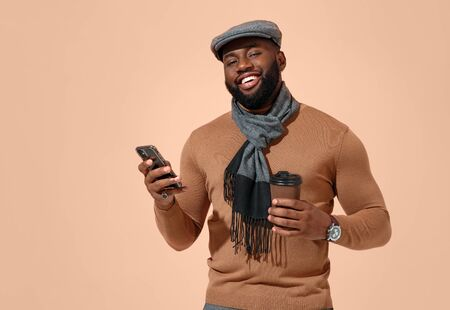 Handsome man uses the phone, checks for new message. Photo of african man in stylish casual clothes on beige background.