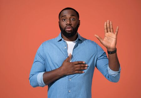 Honest serious man keeps one hand on heart and raises palm, promises or swears to do something. Photo of african man in casual outfit on coral background.