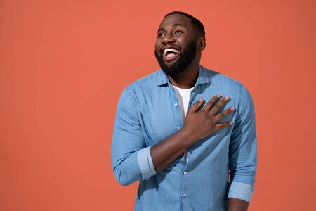 Overjoyed man holding his hands on heart can't stopping laughing. Photo of african man in casual outfit on coral background.