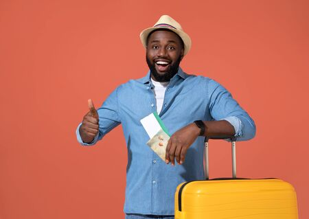 Man traveler with tickets and suitcase. Photo of african man in casual outfit on coral background. Zdjęcie Seryjne