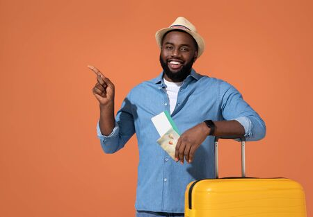 Man traveler with tickets and suitcase, points away. Photo of african man in casual outfit on coral background.