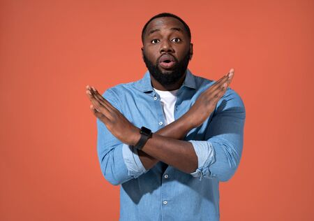 Man raises palms in no or stop gesture. Photo of african man in casual outfit on coral background.