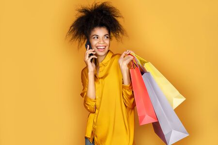 Happy girl holds shopping bags and talks by mobile phone. Photo of african american girl on yellow background 版權商用圖片
