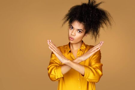 Girl raises arms in no or stop gesture. Photo of african american girl on beige background Фото со стока
