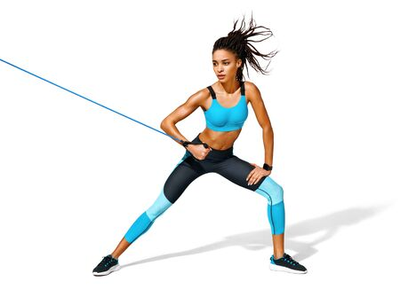 Strong girl working with resistance band. Photo of african american girl in fashionable sportswear on white background. Dynamic movement. Full length. Sports and healthy lifestyle 版權商用圖片