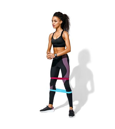 Sporty woman doing squats with resistance band. Photo of african american girl in black sportswear on white background. Strength and motivation