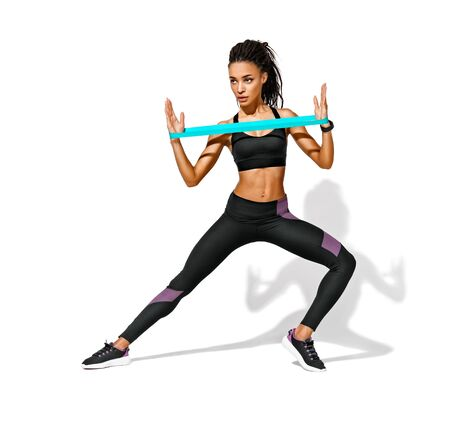 Athletic girl performs exercises using resistance band. Photo of african american girl in black sportswear on white background. Strength and motivation