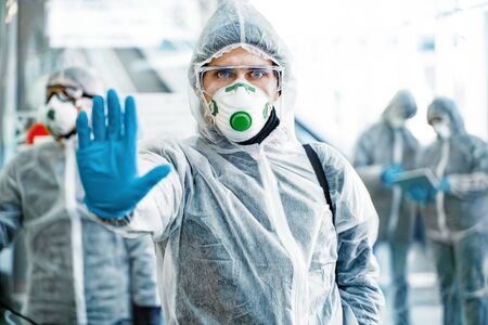 Healthcare worker showing stop gesture. Team of healthcare workers wearing hazmat suits working together in shopping centre, to control an outbreak of virus in the city