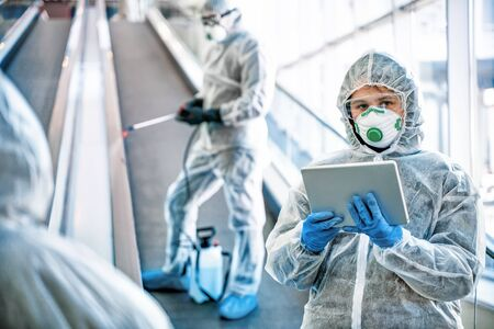 Healthcare workers wearing hazmat suits working together in shopping centre, to control an outbreak of virus in the city