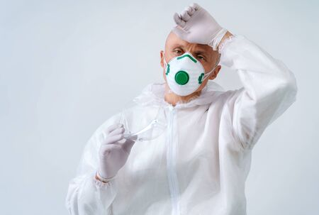 Tired worker in protective suit and medical mask on white background Stok Fotoğraf