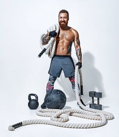 Tired man with heavy rope on his shoulder and dumbbells, medicine ball, kettlebell on the floor. Photo of sporty muscular man with perfect body on white background. Best cardio workout. Archivio Fotografico