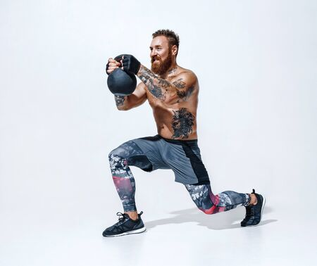 Sporty man doing lunges with kettlebell. Photo of man with torso on white background. Strength and motivation