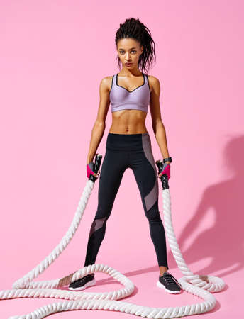 Sweaty girl resting after working out with ropes. Photo of african american girl with perfect body on pink background. Strength and motivation. Full length